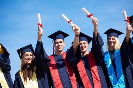 graduacion: grupo de jóvenes estudiantes de pie en frente del edificio de la universidad el día de graduación graduados