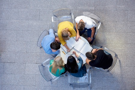 aerial: top view,  group of students together  at school table working homework and have fun