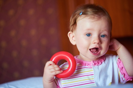 baby toys: happy baby with first teeth smilling and play with toys
