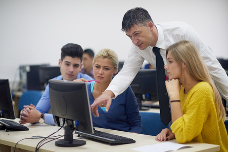 computer lessons: group of students with teacher in computer lab classrom learrning lessons,  get help and support