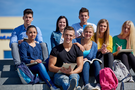 youth group: Group portrait  of happy  students outside in front of school sitting on steps have fun