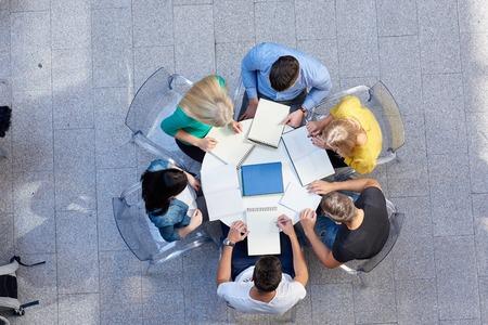 deberes: vista superior, grupo de estudiantes junto a la mesa de la escuela la tarea de trabajar y divertirse