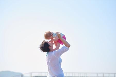 apoyo familiar: feliz mamá y bebé en la playa se divierten mientras aprenden a caminar y hacer los primeros pasos