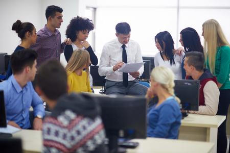 grupo de alumnos con el maestro en classrom laboratorio de computación learrning lecciones, obtener ayuda y apoyo