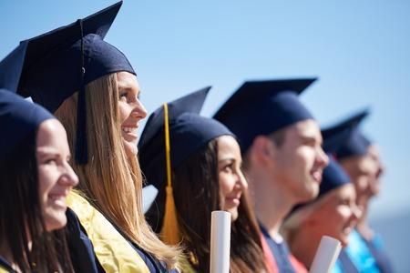 jonge afgestudeerden studenten groep staan in de voorkant van de universiteit gebouw op afstuderen dag