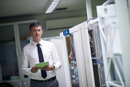 cable red: ingeniero de redes de trabajo en la sala de servidores, hombre de negocios corporativo trabajo en la computadora de la tableta Foto de archivo