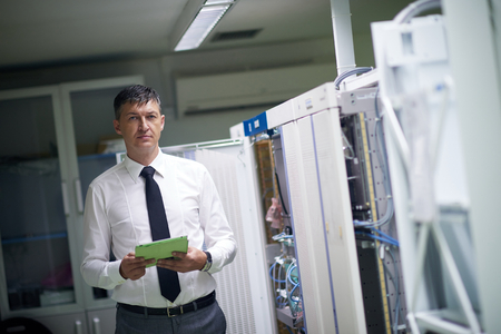 network server: network engineer working in  server room, corporate business man working on tablet computer