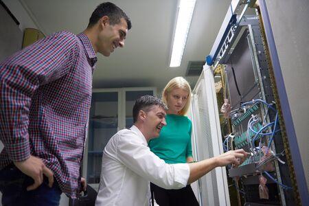 group network: business people group, network engeneers working in network server room on tablet computer