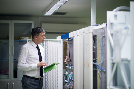 database server: network engineer working in  server room, corporate business man working on tablet computer