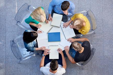 persona sentada: vista superior, grupo de estudiantes junto a la mesa de la escuela la tarea de trabajar y divertirse