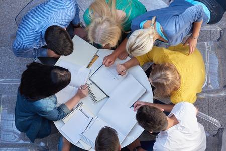 mujeres juntas: vista superior, grupo de estudiantes junto a la mesa de la escuela la tarea de trabajar y divertirse