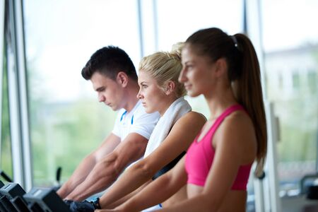 young friends: Beautiful group of young women friends  exercising on a treadmill at the bright modern gym Stock Photo