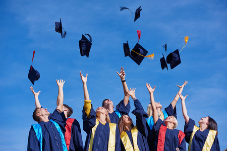 graduate: high school students graduates tossing up hats over blue sky. Stock Photo