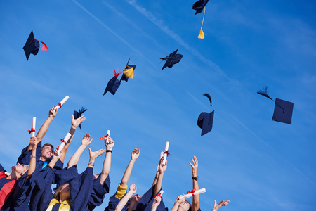 gown: high school students graduates tossing up hats over blue sky. Stock Photo