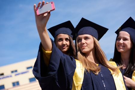 Capturing a happy moment.Students group  college graduates in graduation gowns  and making selfie photo