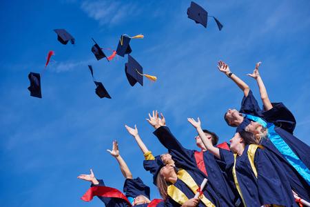 GRADUADO: estudiantes de secundaria graduados, lanzando hasta sombreros sobre el cielo azul.