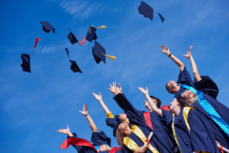 graduation: high school students graduates tossing up hats over blue sky. Stock Photo