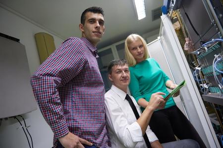 isp: business people group, network engeneers working in network server room on tablet computer