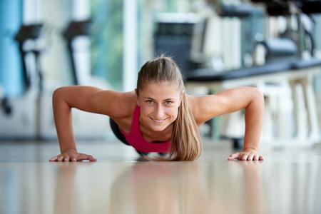 Prachtige blonde vrouw warming up en het doen van wat push ups een de sportschool