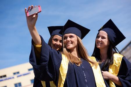 graduacion: La captura de un feliz graduados universitarios grupo moment.Students en vestidos de graduaci�n y haciendo selfie foto Foto de archivo
