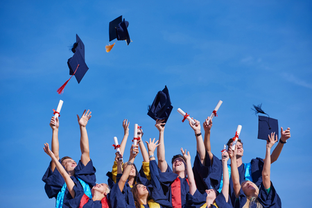 cap and gown: high school students graduates tossing up hats over blue sky. Stock Photo
