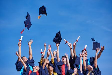 middelbare scholieren afgestudeerden heen up hoeden over blauwe hemel. Stockfoto
