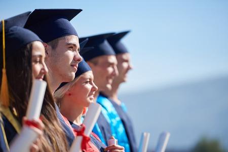 high: grupo de jóvenes estudiantes de pie en frente del edificio de la universidad el día de graduación graduados