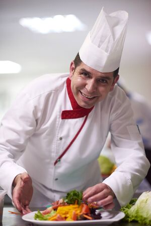 hotel service: chef in hotel kitchen preparing and decorating food, delicious vegetables and meat  meal dinner Stock Photo