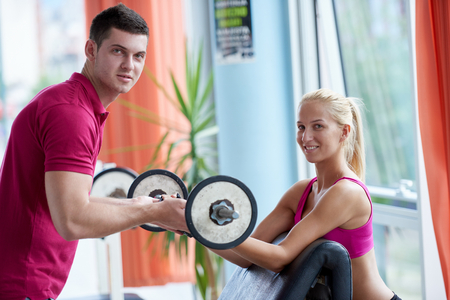 young guy: young sporty woman with trainer exercise weights lifting in fitness gym