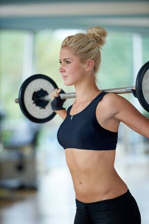 woman muscle: healthy and fit young woman in fitness gym lifting weights and working on her butt muscles
