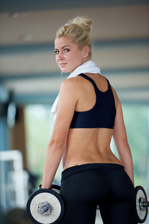 pesas: Gorgeou chica mujer levantando unas pesas y trabajar en sus bíceps en un gimnasio
