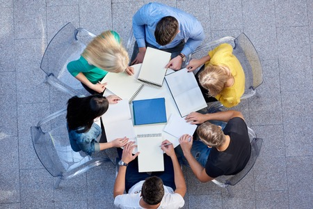 work group: top view,  group of students together  at school table working homework and have fun