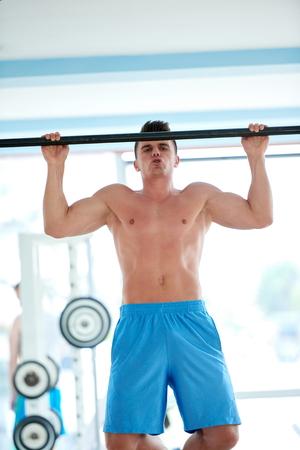 fitness hombres: hombre joven y guapo en el gimnasio de fitness levantando y colgando mientras se trabaja en las manos y los músculos de la espalda