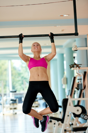 pull up: healthy lifestile, young woman in fitness gym lifting on bar and working on her back and hands muscles