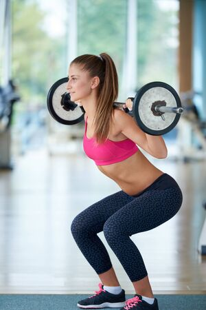fitness gym: healthy and fit young woman in fitness gym lifting weights and working on her butt muscles
