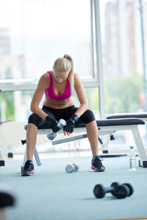 Weights: halethy young woman exercise with dumbells and relaxing on banch in fitness gym