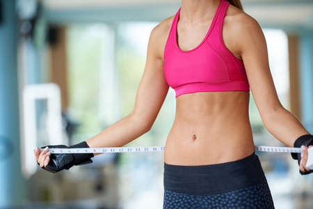 sexy female: young fit woman measuring belly on a training  in  fitness gym Stock Photo