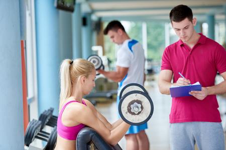 pesas: joven mujer deportivo con pesas ejercicio entrenador levantar en el gimnasio de fitness Foto de archivo