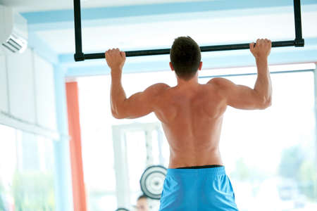 hang body: handsome young man in fitness gym lifting up and hanging while working on hands and back muscles Stock Photo
