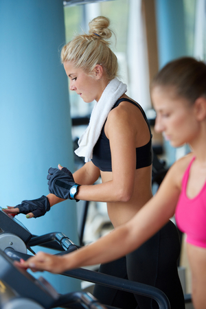 fitness gym: sport, fitness, lifestyle, technology and people concept - smiling woman exercising on treadmill in gym
