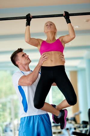 pull up: trainer support young woman while lifting on bar in fitness gym indoors