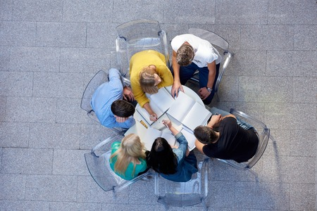 teams: top view,  group of students together  at school table working homework and have fun
