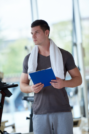 copies: Portrait of a smiling male trainer with clipboard standing in a bright gym