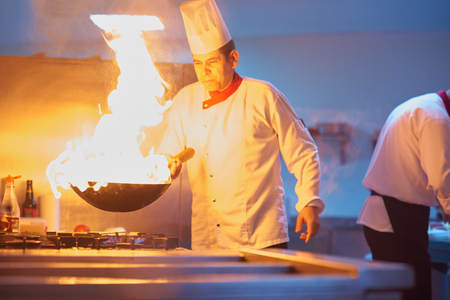 chef kitchen: chef in hotel kitchen prepare vegetable  food with fire