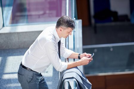 businessman in office: business man using phone at modern office space