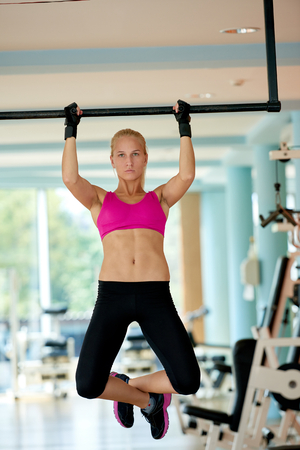 lifestile: healthy lifestile, young woman in fitness gym lifting on bar and working on her back and hands muscles