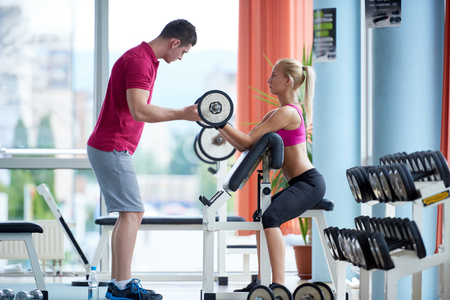 Weights: young sporty woman with trainer exercise weights lifting in fitness gym