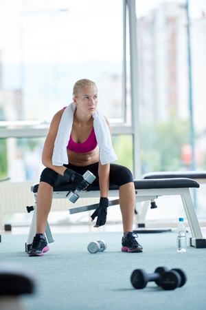fitness gym: halethy young woman exercise with dumbells and relaxing on banch in fitness gym