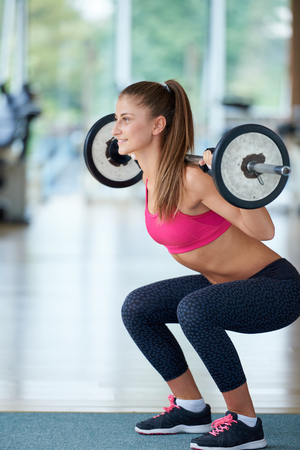 healthy and fit young woman in fitness gym lifting weights and working on her butt muscles