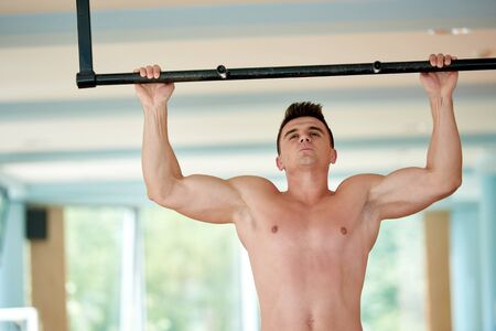 pull up: handsome young man in fitness gym lifting up and hanging while working on hands and back muscles Stock Photo